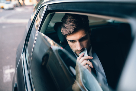 Young businessman sitting on back seat of a car with mobile phone and thinking. Caucasian male business executive travelling by a cab. Stock Photo