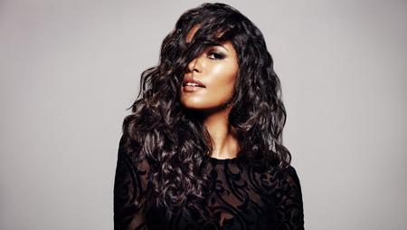 Belle femme brune aux longs cheveux bouclés. Femme de race mixte avec une coiffure ondulée sur fond gris. Banque d'images