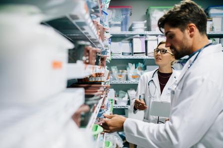 두 약사 약국에서 일하고입니다. 남성과 여성의 약사 병원 약국에서 의약품 재고를 확인합니다.