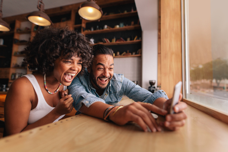 Young couple sitting together at coffee shop and taking selfie using smart phone. Young man and woman laughing while taking selfie in cafe