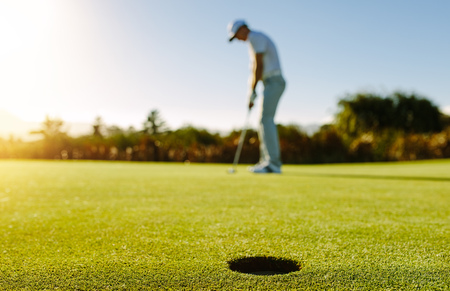 Golf player putting ball in hole. Horizontal shot of golf hole in the green field with golfer in background.