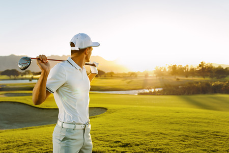 Shot of male golfer with golf club at course. Young man holding a golf club and looking away on a sunny day.