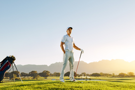 Full length of male golfer on golf course waiting to tee off. Man playing golf on field on a sunny day. Banco de Imagens