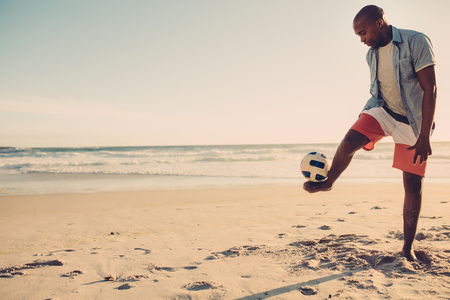 Afro american man playing with football along the beach. Black male balancing a soccer ball on his feet at the sea shore. Stock fotó