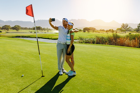Young couple taking self portrait on putting green at golf course. Male and female golfers taking selfie with mobile phone at field on sunny day.