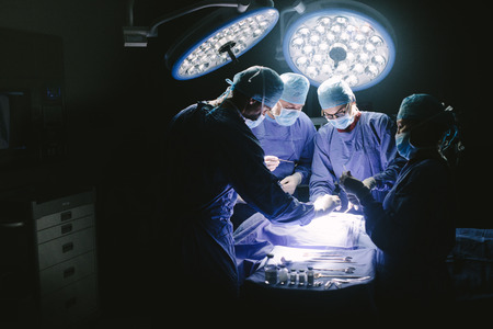 Doctors during surgery on patient in hospital. Surgeons team working at the hospital performing surgical procedure in operating theatre.