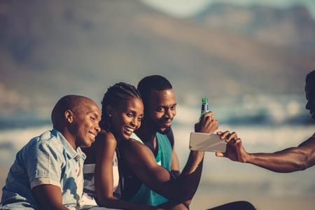 Grupo de amigos felices divirtiéndose juntos y tomando selfie usando el teléfono móvil. Autorretrato en la fiesta en la playa.
