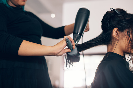 Female hairdresser using blower and brush to dry hair. Hair stylist using dryer on woman wet hair in salon. Banco de Imagens