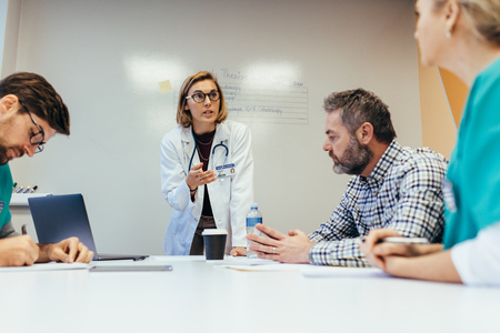 Empowerment van vrouwen. Vrouwelijke arts die een vergadering met haar personeel in bestuurskamer leidt. Vrouw medische professional briefing haar collega's.