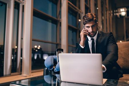 Jonge zakenman die aan laptop werkt en op mobiele telefoon in de luchthaventerminal spreekt. Knappe Kaukasische zakenman die op zijn vlucht bij luchthavenzitkamer wacht. Stockfoto