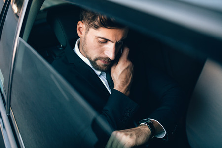 Young businessman talking on the mobile phone and looking at the watch while sitting on back seat of car. Caucasian business executive checking time and making phone call in car.