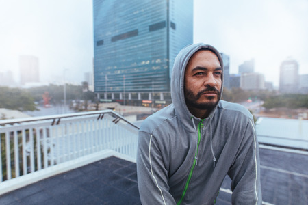 Man in hooded sweatshirt looking away. Man on top of a building against a blurred cityscape.