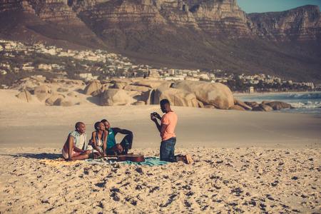 Afrikaanse jonge man fotograferen vrienden telefonisch buitenshuis op het strand. Knappe man die foto's van zijn vrienden van smartphone maakt. Stockfoto