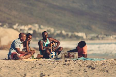 Afroamerikanischer junger Mann mit Gitarre singt ein Lied für seine Freunde. Gruppe von Freunden im Urlaub entspannen am Strand. Standard-Bild - 84512448