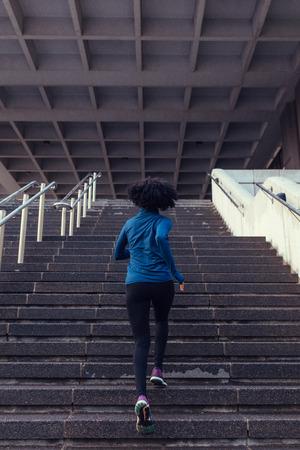 Femme qui court les escaliers d'un immeuble. Femme athlète monter des escaliers dans le cadre de son entraînement physique. Banque d'images - 84577748