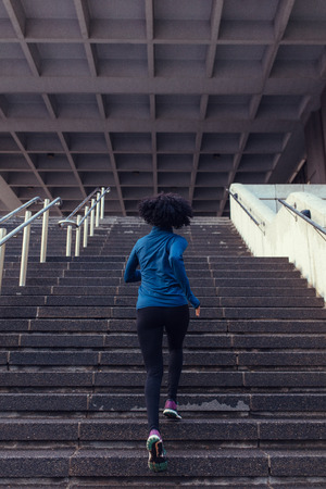 Woman running up the stairs of a building. Woman athlete climbing stairs as part of her physical training. Reklamní fotografie