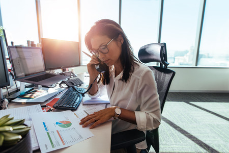 Woman entrepreneur looking at business papers while talking over phone. Woman sitting at her desk in office working with papers while seated in front of desktop computers.