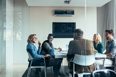 Female manager leads brainstorming meeting in design office. Businesswoman in meeting with colleagues in conference room. Stock Photo