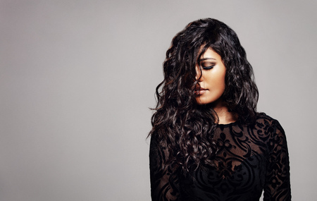 Stylish young woman with curly hair against grey background.