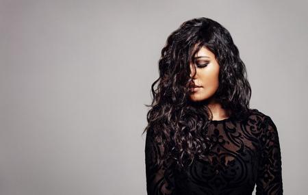 회색 배경에 곱슬 머리와 세련 된 젊은 여자.