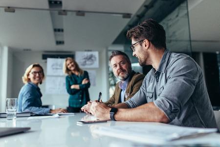 Zakenman die ideeën op project in conferentieruimte deelt. Groep bedrijfsmensen in vergadering op kantoor.