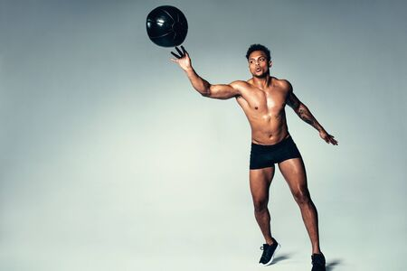 Shot of fit young man exercising with medicine ball. Stock Photo