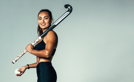 Portrait of beautiful young woman holding hockey stick and ball against grey background. Hispanic female hockey player looking at camera.