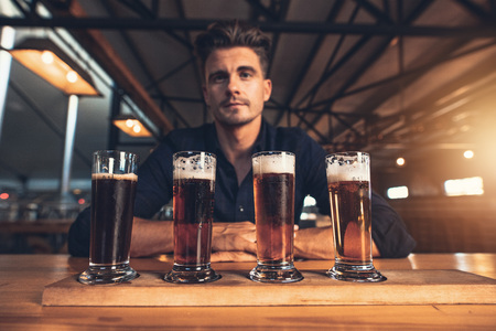 Young man tasting different varieties of craft beer on a wooden table at brewery. Master brewer with different types of beers at bar table.