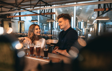 Young man and woman at the bar with different types of beers. Couple at brewery bar and tasting beers.