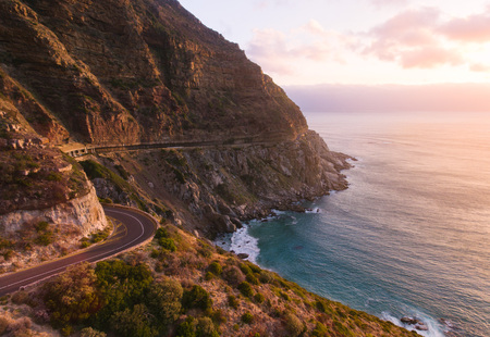Beautiful road going along the mountain and oceans. Amazing sunset scene. Imagens