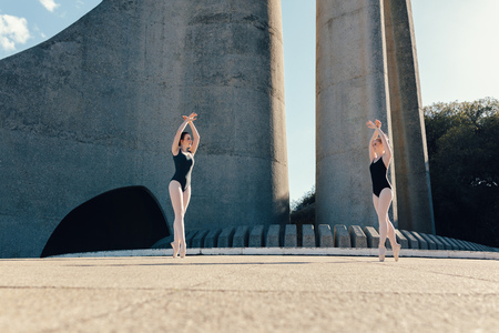 coordinacion: Ballet dancers practicing dance moves outdoors. Ballet dancers performing a duet in synchronization.