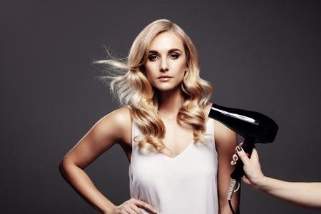 Portret van jonge schitterende blonde vrouw die zich op grijze achtergrond met haar haar bevindt dat door droger wordt geblazen.