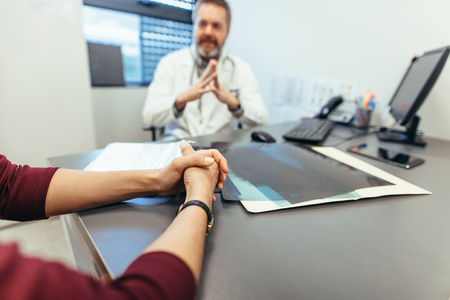 Female sitting at table in clinic with doctor in background. Focus on woman patient hands visiting doctor. Woman meeting with medical doctor to seek advice. Stock Photo
