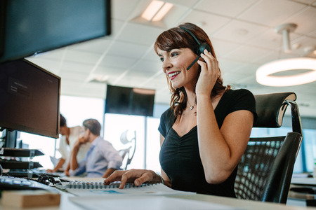 Call center business woman talking on headset. Caucasian female in customer service position talking on the phone. Archivio Fotografico