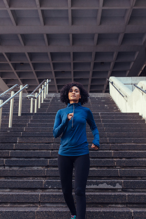 Woman in tracksuit running in city. Woman athlete climbing down stairs as part of her physical training.