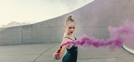 Ballet artist practicing dance moves outdoors using a pink smoke bomb. Female ballet dancer using a firework as a prop in her dance.