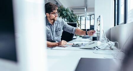 コンピューターのモニターにポストイットを置く青年実業家。近代的なオフィスに彼の机で働く白人男性。 写真素材