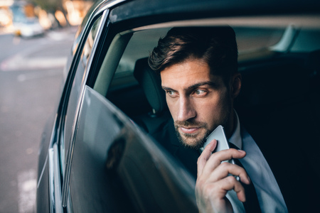 Young businessman looking away while sitting on the back seat of a car. Business executive thinking and looking outside window of taxi. Stock Photo