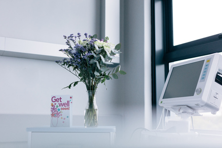 Get well soon wishing card with flower vase on side table in hospital room. Фото со стока