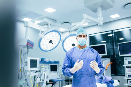 Portrait of male surgeon standing in operating room, ready to work on a patient. Male medical worker surgical uniform in operation theater. Stockfoto