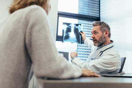 医師は、医療事務に彼の患者に x 線を示します。患者の診察室に座っていると x 線画像の診断を議論する医師。 写真素材