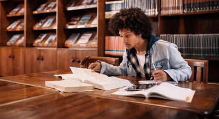 Jonge afro Amerikaanse student die voor het examen in de bibliotheek voorbereidingen treft. College student studeert in de bibliotheek. Stockfoto