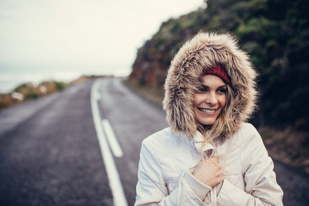 Portrait of beautiful smiling woman on open highway. Woman in fur hat and jacket on beautiful winter day.