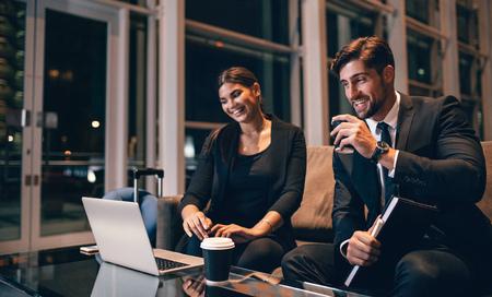 Jeune homme d'affaires et femme attendant au salon de l'aéroport et regardant un ordinateur portable. Les voyageurs d'affaires en attente de leur vol au terminal de l'aéroport.
