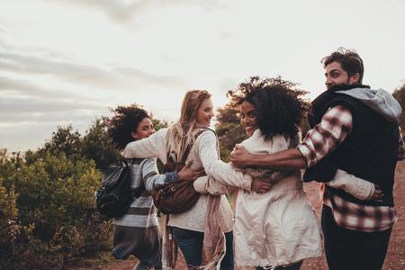 Freunde, die in der Natur wandern. Gruppe von Männern und Frauen, die zusammen in der Landschaft gehen. Glückliche junge Leute, die herum drehen und Kamera betrachten. Standard-Bild - 85318513