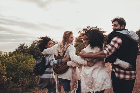 Friends hiking in nature. Group of man and women walking together in countryside. Happy young people turning around and looking at camera. Stockfoto