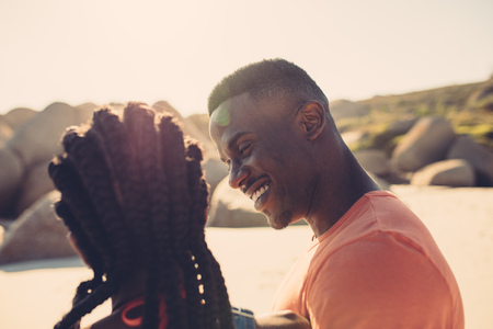 Young man looking at his girlfriend at the beach. African couple along the seashore on a summer day.