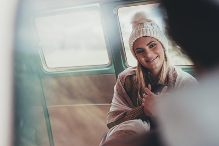 Woman travelling by van with friend. Caucasian female wearing warm clothing sitting in back seat of van holding coffee and smiling.