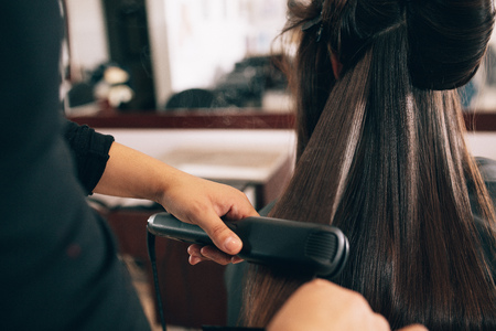 Hairdresser using a hair straightened to straighten the hair. Hair stylist working on a womans hair style at salon.