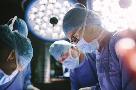 그녀의 팀 병원 수술실에서 수술을 수행하는 집중된 여성 외과. 운영 극장에서 수술하는 동안 의료진입니다.